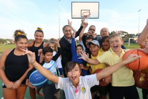Randwick Mayor Noel D'Souza, Councillor Ted Seng and Youth Advisory Committee member Adry Awan with local young people at the opening of the Coral Sea Park basketball court.